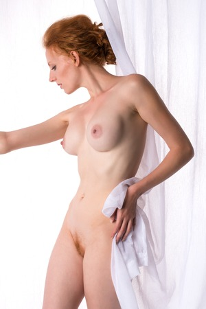 Beautiful tall redhead nude behind a white curtain