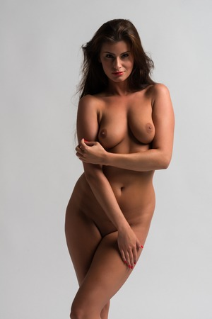 Beautiful Czech woman standing nude on gray