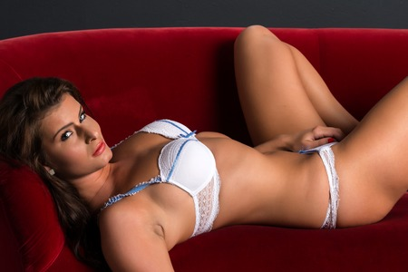 red sofa: Beautiful Czech woman in white lingerie on a red plush couch