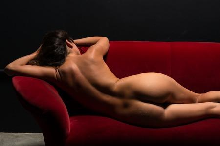Hermosa morena delgada desnuda en un sofá rojo
