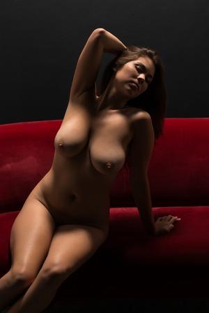 mujer desnuda sentada: Mujer eurasiática joven hermosa que se sienta desnuda en un sofá rojo de felpa Foto de archivo