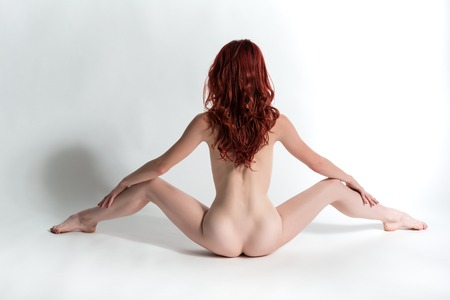 Slender young redhead nude on white Stock Photo