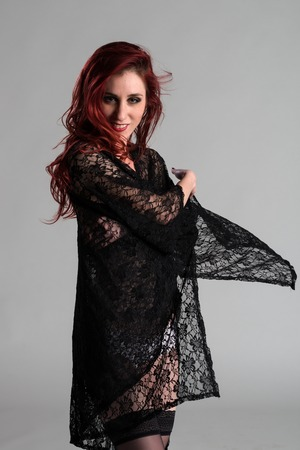 Slender young redhead covered with black lace