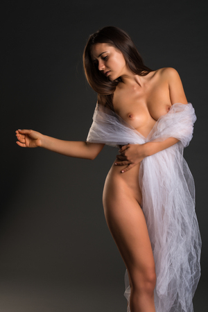 Pretty young Romanian woman standing nude on gray photo
