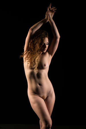 Shapely redheaded woman standing nude in deep shadow