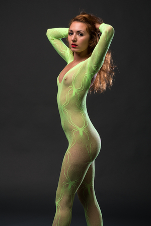 Slender young redheaded woman in a green fishnet body stocking