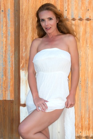 strapless: Beautiful tall redhead in a strapless white dress Stock Photo