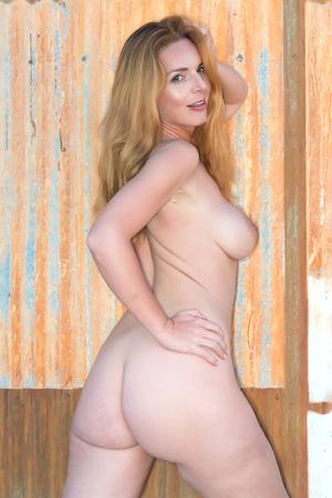 femme se deshabille: Belle grande rousse nue contre un mur de t�le ondul�e