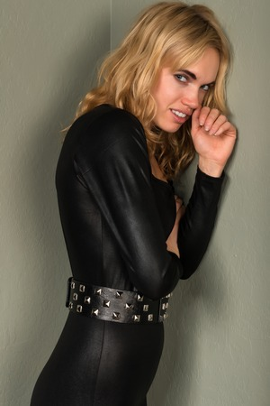 Beautiful young blonde woman in a shiny black catsuit