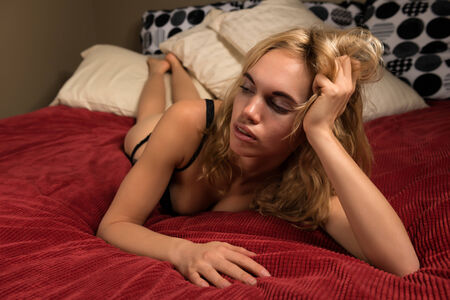 bedspread: Beautiful young blonde woman in black lingerie