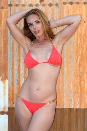 tall woman: Beautiful tall redhead in an orange bikini