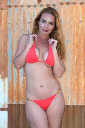 female sexy chains: Beautiful tall redhead in an orange bikini