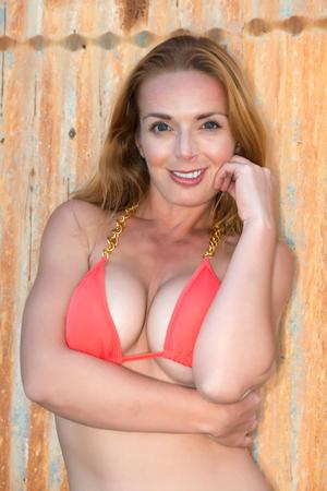 Beautiful tall redhead in an orange bikini