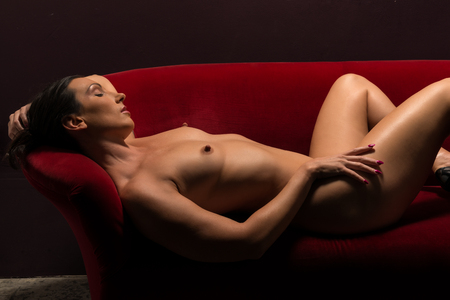 Beautiful athletic brunette lying nude on a red couch photo
