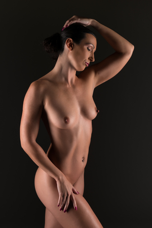 Beautiful athletic brunette nude in shadow photo