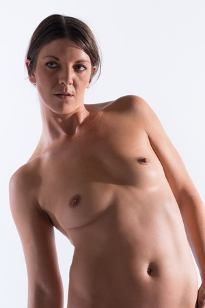 Athletic tanned brunette standing nude on white