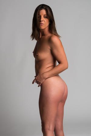 femme se deshabille: Athletic brune bronz�e nu debout sur fond gris