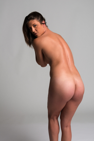 Athletic tanned brunette standing nude on gray