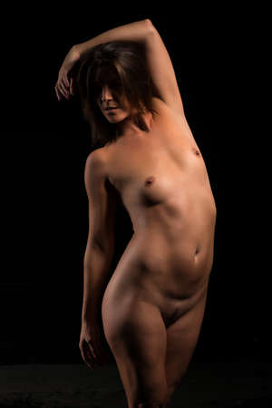 Athletic tanned brunette standing nude on black