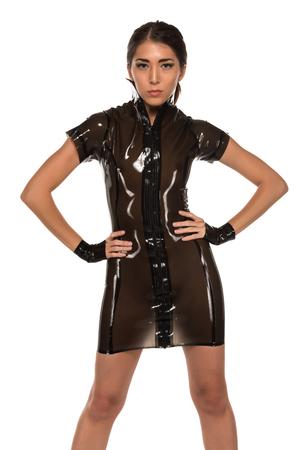 Beautiful petite Eurasian woman in a brown latex dress