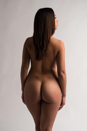 femme se deshabille: Belle Latina tann�e nue sur fond gris Banque d'images