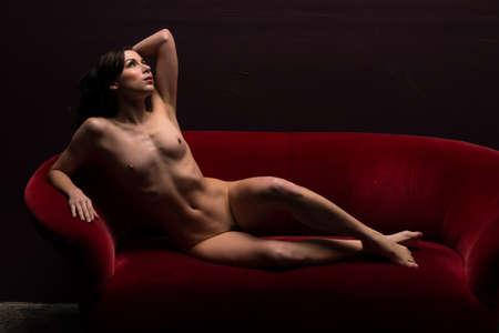 chica desnuda: Bastante joven morena desnuda acostada en un sofá rojo Foto de archivo