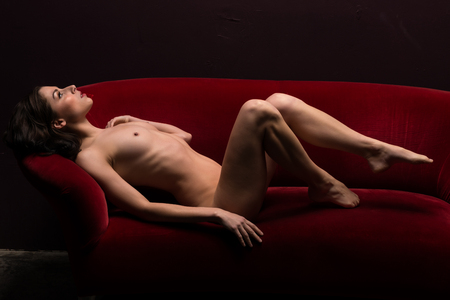 topless: Pretty young brunette lying nude on a red couch