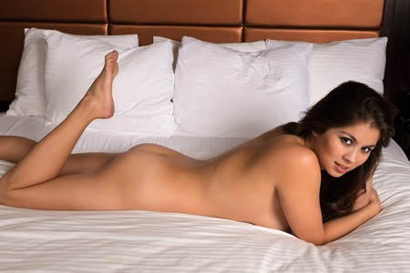 nudity young: Beautiful young Eurasian woman lying nude in bed