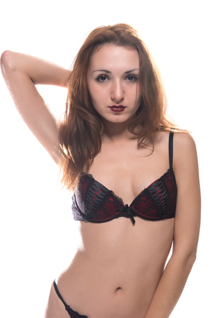undergarment: Slender young redheaded woman in red and black lingerie