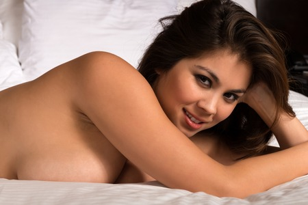 nude: Beautiful young Eurasian woman lying nude in bed