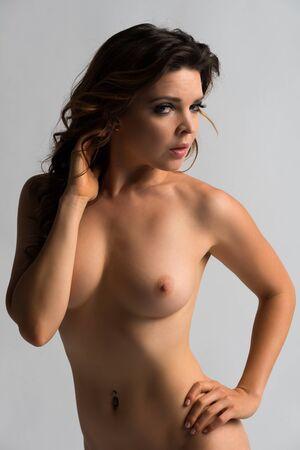 femme se deshabille: Jolie petite brune nue sur fond gris