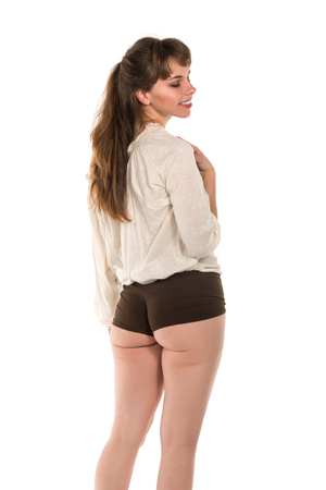 Pretty young brunette in a beige blouse and brown panties