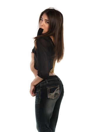 Beautiful petite Eurasian woman in a black blouse and jeans
