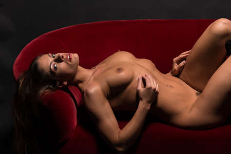 female nudity: Beautiful athletic brunette lying nude on a red couch