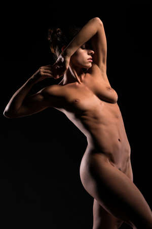 in the nude: Bello atletico bruna in piedi nudo in ombra