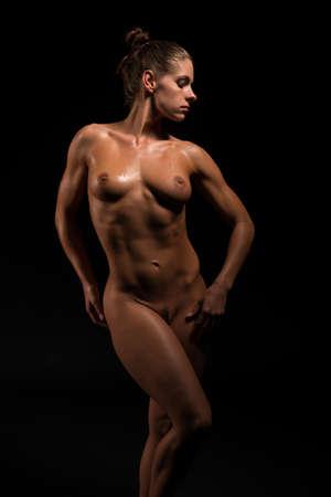 female nudity: Beautiful athletic brunette standing nude in deep shadow