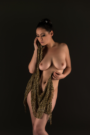Beautiful nude multiracial woman wrapped in gold fabric Stock Photo