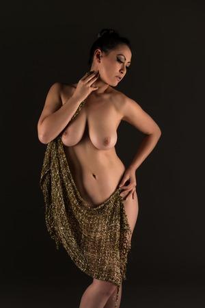 mujeres morenas: Hermosa mujer multirracial desnuda envuelta en tela de oro Foto de archivo