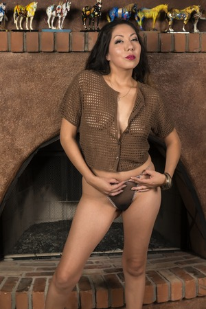 Pretty petite Native American woman in front of a fireplace