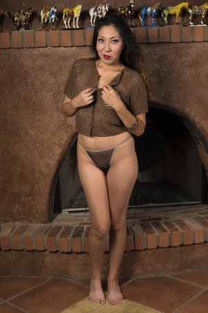 native american woman: Pretty petite Native American woman in front of a fireplace