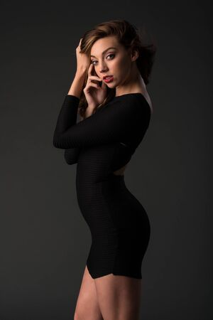 Beautiful young brunette in a tight black dress