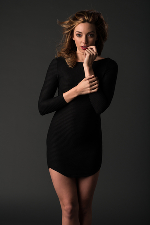 tight dress: Beautiful young brunette in a tight black dress
