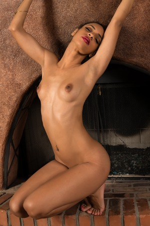Beautiful young multiracial woman nude in a fireplace