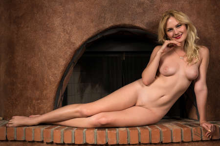 Beautiful tall Russian blonde sitting nude in a fireplace