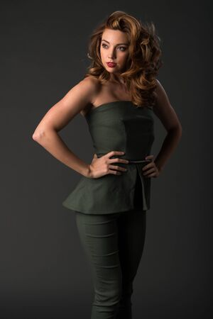 strapless: Beautiful young brunette in a dark green pantsuit