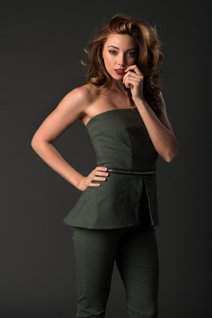pantsuit: Beautiful young brunette in a dark green pantsuit