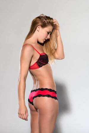 Pretty petite blonde in red and black lingerie photo