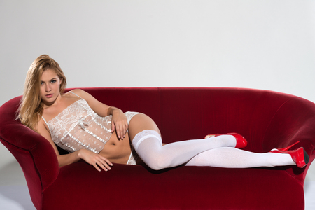 Pretty petite blonde in white lingerie on a red couch