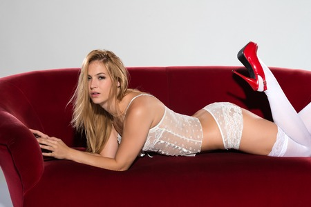 panty hose: Pretty petite blonde in white lingerie on a red couch