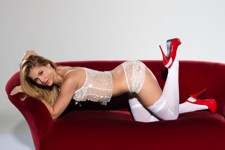 red couch: Pretty petite blonde in white lingerie on a red couch